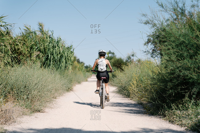 Full body of positive young female cyclist in sportswear and helmet riding bicycle on dirt path among green plants in summer day in countryside