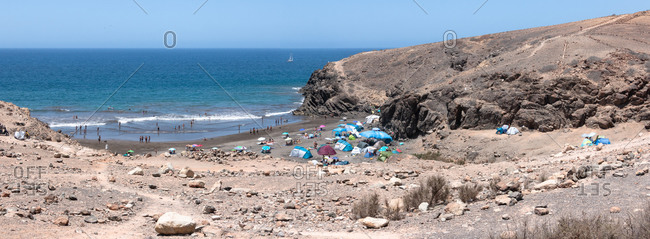 Scenery of a rocky beach full of people in the island of Gran Canaria