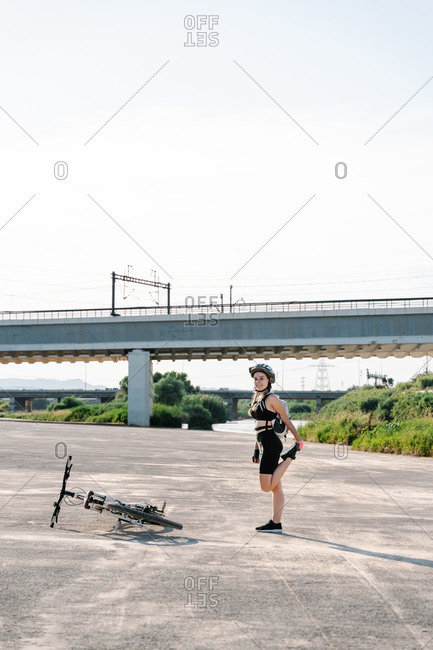 Cheerful young female in active wear and helmet standing on asphalt path near bicycle and stretching legs while preparing for trip in summer day