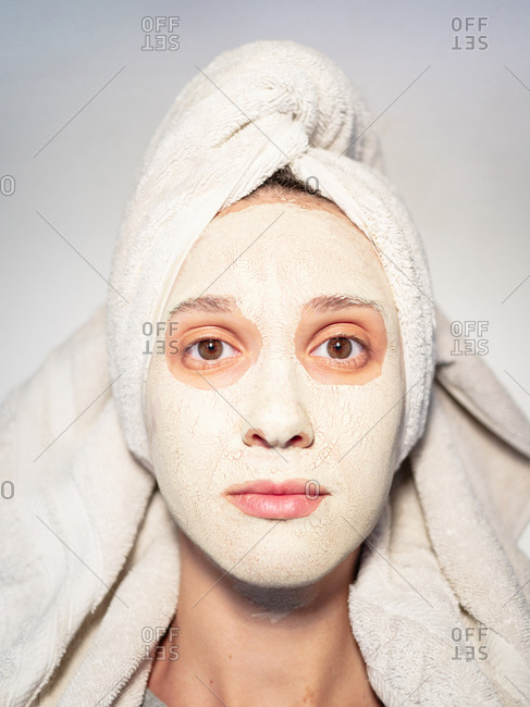 Closeup portrait woman facial mud mask hair wrapped in towel