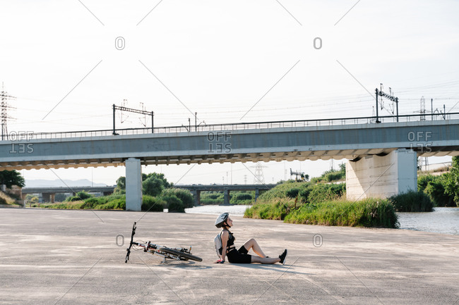 High angle side view of happy young woman in sportswear and helmet with backpack sitting on paved ground and resting after riding bike in summer day