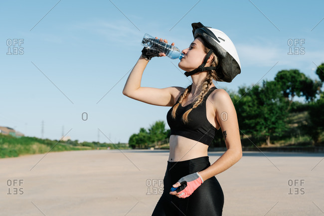 Side view of slim young female in sportswear and bicycle helmet drinking water from plastic bottle while resting during riding bike in summer day in countryside