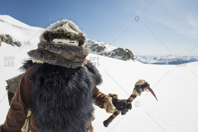 Native American hunter holds Traditional ax tool in mountains.