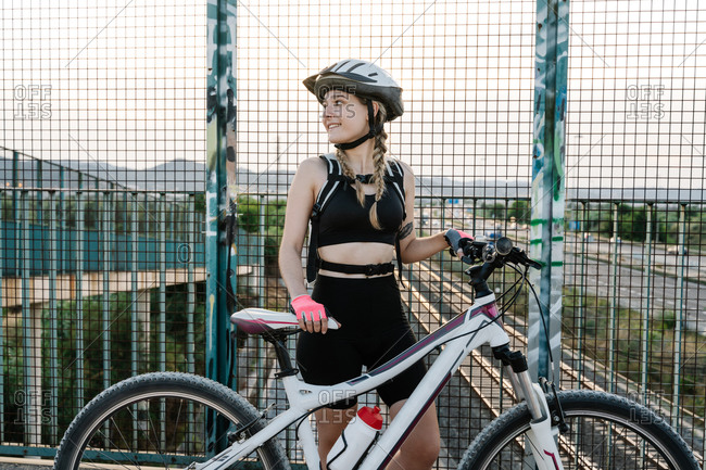 Female bicyclist in protective helmet and gloves standing near grate fence on bridge over road with blurred hills in background