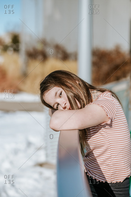 Vertical portrait of preteen resting head on the side of ice rink