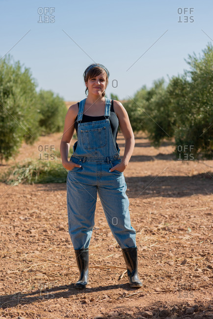 Happy female farmer standing on field with hands on the pocket while working in village in summer looking at camera