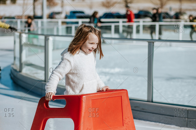 Young girl learning how to ice skate on a sunny winter day