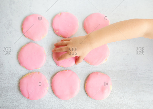 Top view of child's hand grabbing pink sugar cookie off of table