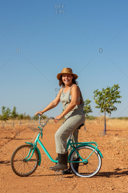 Serene female in denim overalls and sunglasses standing with bike on sandy road in countryside and looking at camera