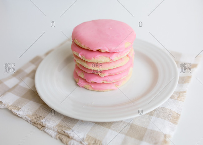 Stack of pink frosted sugar cookies on white plate with neutral colors