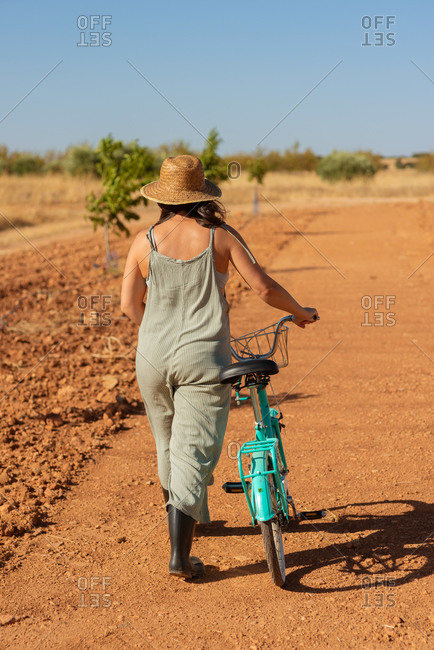 Back view of unrecognizable female in denim overalls and sunglasses walking with bike on sandy road in countryside