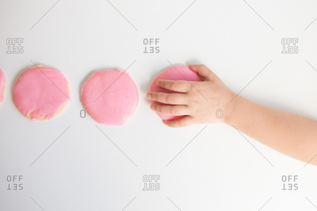 Overhead view of child's hand taking pink frosted sugar cookie