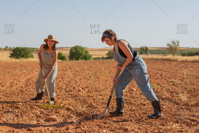 Females farmers in sunhat using rake on ground of field while working in village in summer
