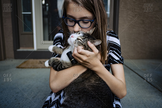 Pre teen girl kissing her cat on the front porch