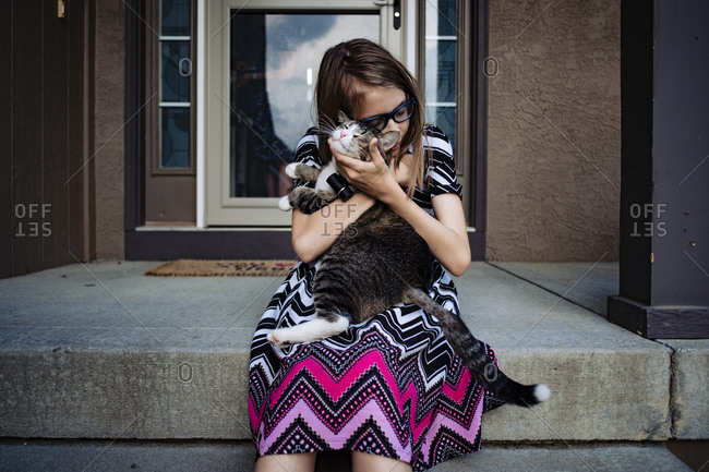 Pre teen girl snuggling her cat on the front porch of her house