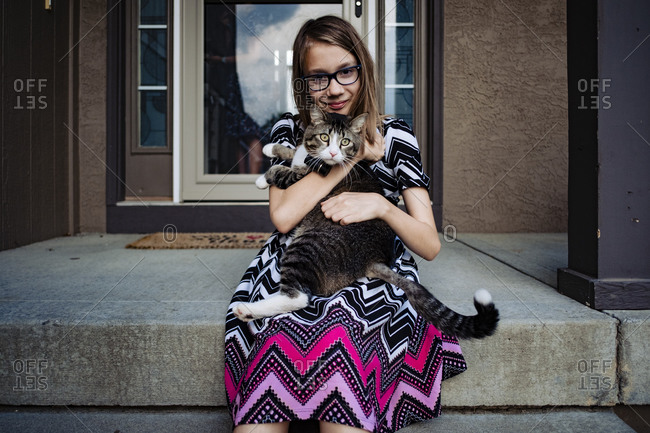 Pre teen girl holding her gray cat on the front porch