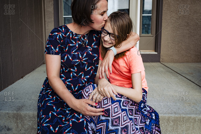 Mom kissing daughter on front porch