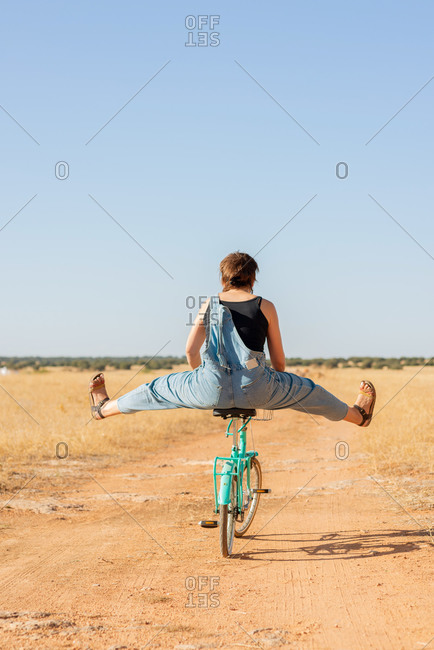 Back view of unrecognizable female in denim overalls and sunglasses riding a bike on sandy road in countryside