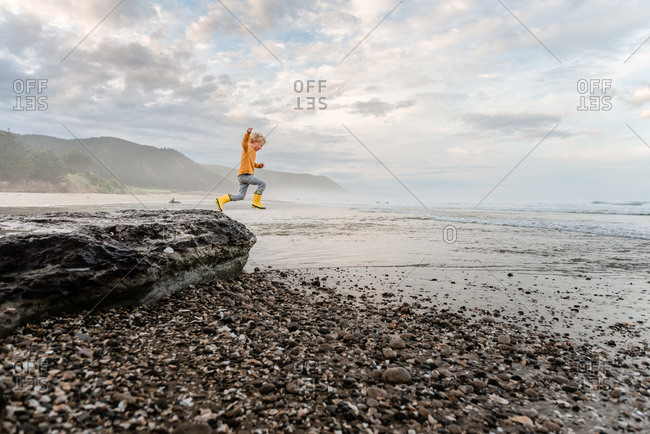 Young curly haired child leaping from rock at beach in New Zealand