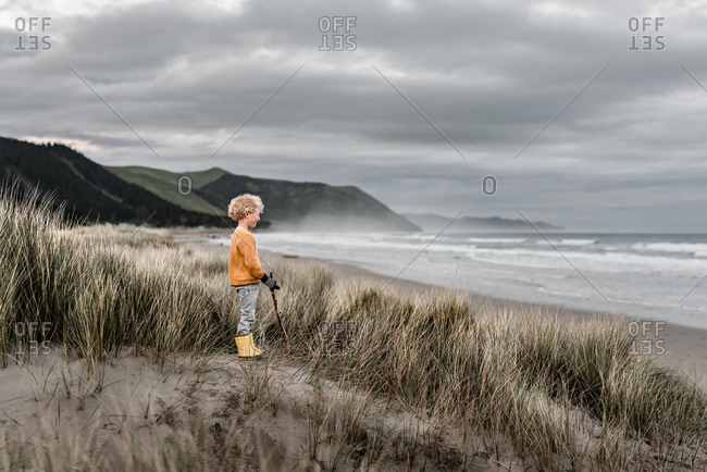 Blond curly haired boy watching ocean on cloudy day in New Zealand