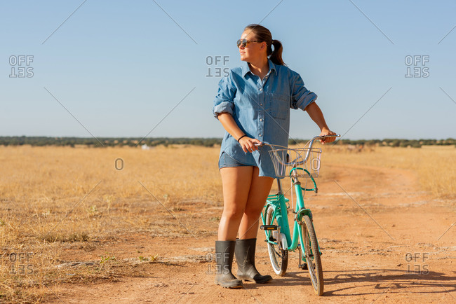 Content female in rubber boots standing with bike on sandy road in countryside and looking away while enjoying weekend
