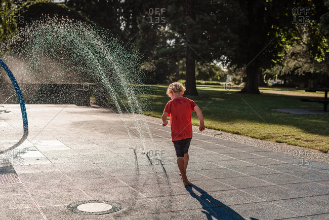 Child playing in a splash park on a summer day