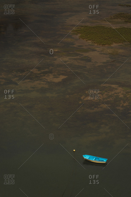 Aerial view of lonely wooden boat floating on calm clean surface of lake
