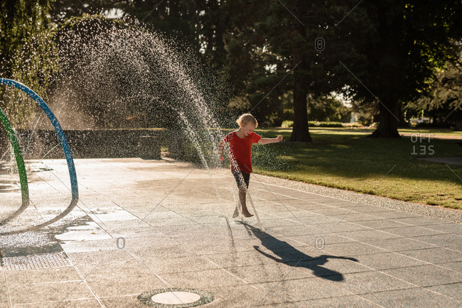Happy child playing in water at a park