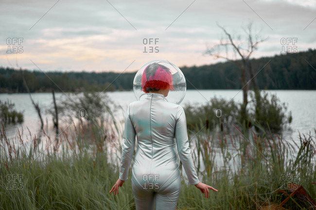 Back view of unrecognizable futuristic young red haired female in silver space suit and glass helmet walking to flooding river