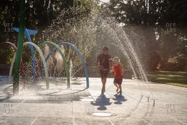 Brothers running in water at playground in New Zealand