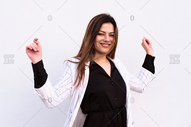 Young woman posing funny in front of a white wall