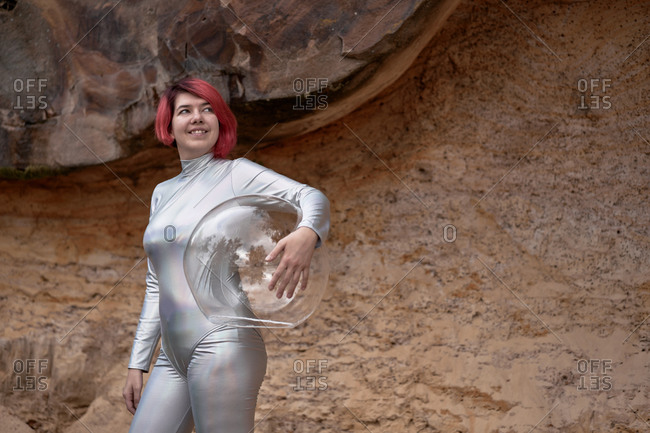 Low angle of positive young female with dyed red hair wearing silver space suit and glass helmet and looking away while walking on rocky formation