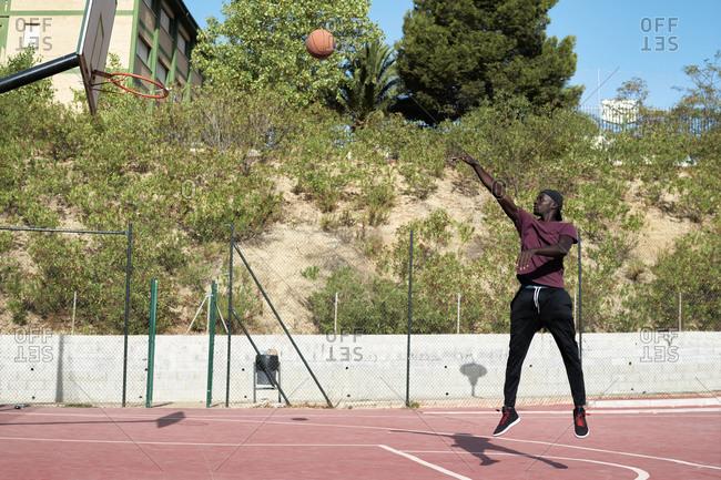 Young black man shooting basketball