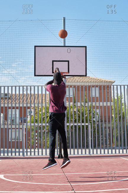 Young black man throwing the ball to the basketball basket