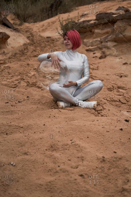 Positive young female with dyed red hair wearing silver space suit and glass helmet and looking away while sitting on rocky formation