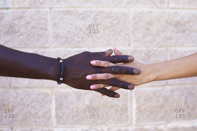 Hand of black man and white woman intertwined