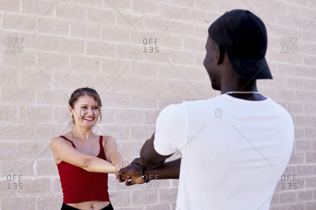 Interracial couple plays and intertwines their arms