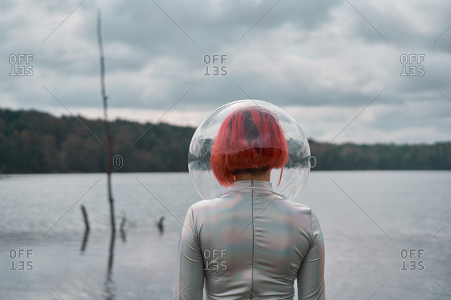 Back view of unrecognizable futuristic young red haired female in silver space suit and glass helmet walking on flooding river