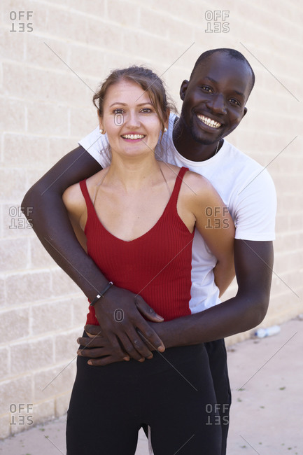 African-American man hugs his white girlfriend