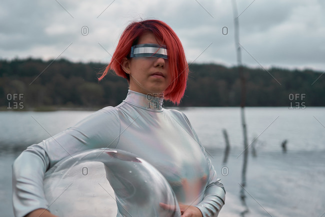 Futuristic young red haired female in silver space suit standing with glass helmet near flooding river