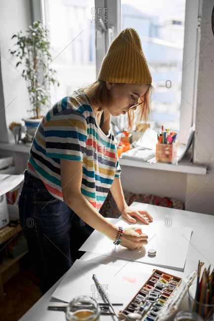 Side view of delighted female artist in trendy wear creating artwork in studio while painting on paper with watercolors