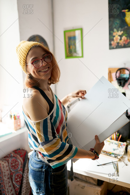 Side view of content female painter in funky outfit standing with art supplies in studio and looking at camera