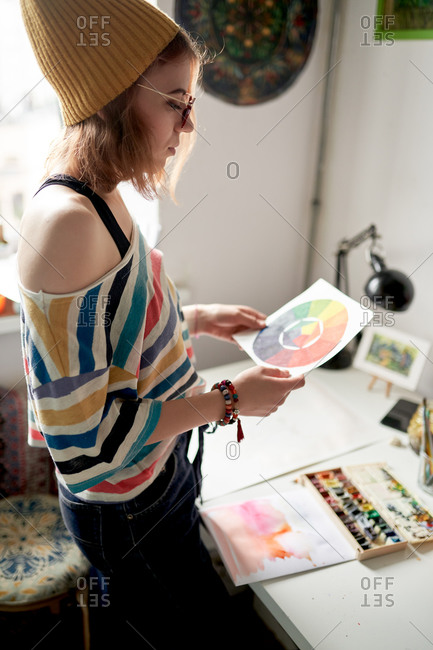 Side view of female artist standing at table with color wheel on paper while working on project in modern art studio