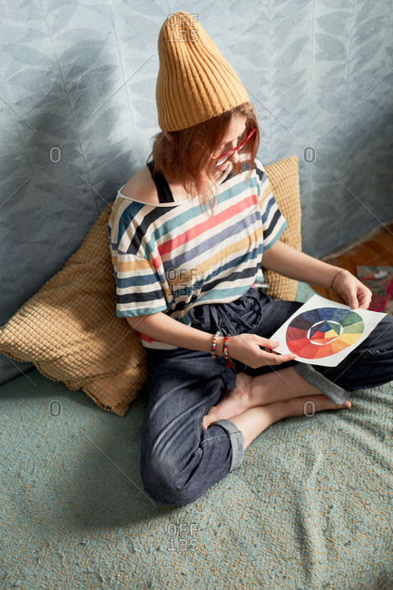 High angle of female artist sitting on bed with color wheel painted with watercolors on paper