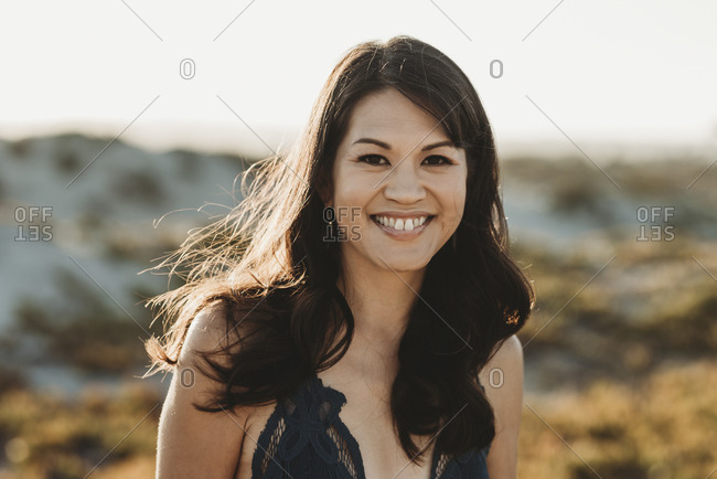 Attractive smiling mid-40's woman with long dark hair wearing lacy top