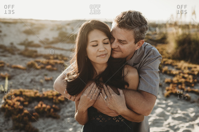 Mid-40's husband embraces beautiful wife with sand dune in background
