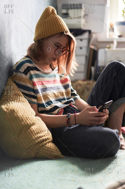 Side view of female millennial in trendy wear sitting on sofa at home and chatting with friends on social media via mobile phone