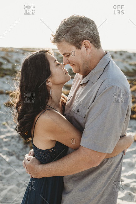 Mid-40's man and woman with closed eyes embracing and touching noses