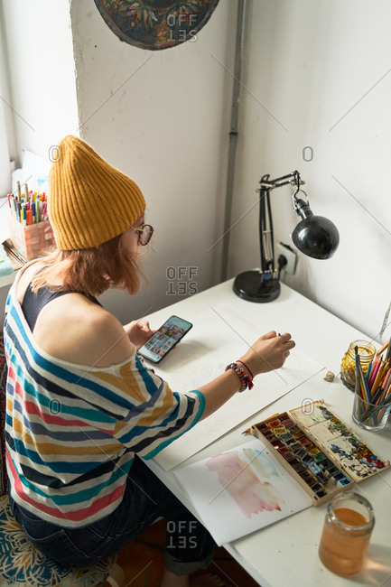 Female artist painting with watercolors and watching online video tutorial on smartphone while creating artwork in studio