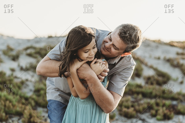 Smiling mid-40's dad hugging young daughter near sand dune